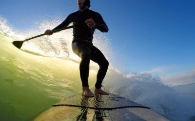 fit man paddle surfing