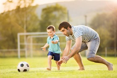 father and son play soccer