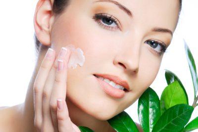 Woman applying moisturizer cream on face. Close-up fresh woman face.