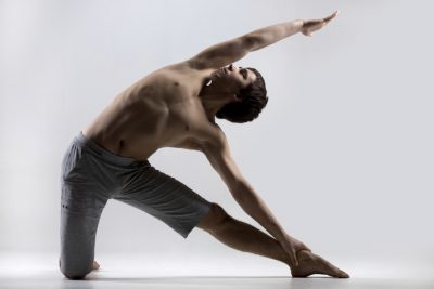 Athletic muscular young man working out, yoga, pilates, fitness training, doing side bend, asana Parighasana, Gate Yoga Pose, gray background, low key shot
