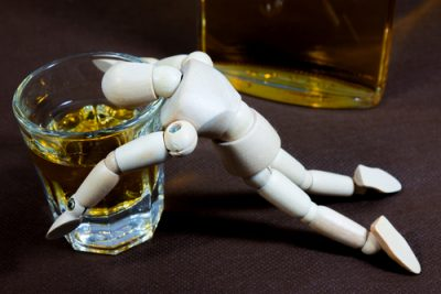 wooden figurine passed out over glass of alcohol