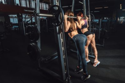 fit women doing barbell squats in gym