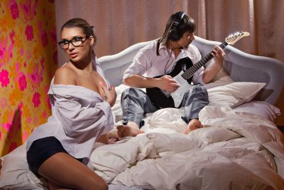 man playing guitar while woman listen with pleasure in bed