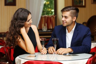 attractive couple in romantic date in restaurant with wine