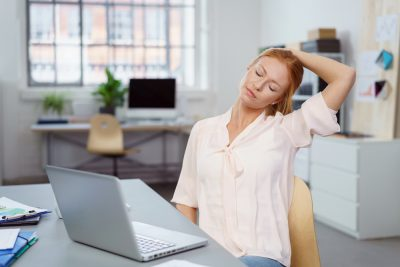 woman stretching in office desk