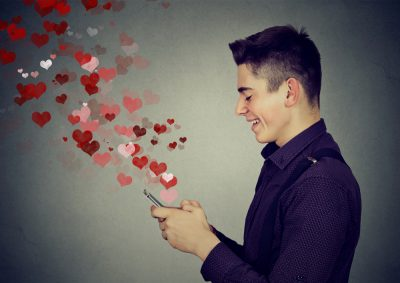 young man texting on phone with hearts, online dating