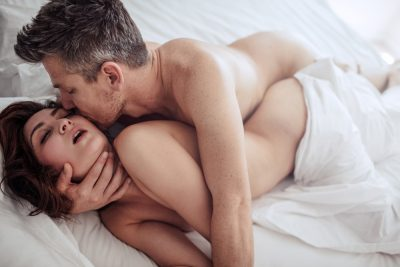 couple having sex in bed, spooning