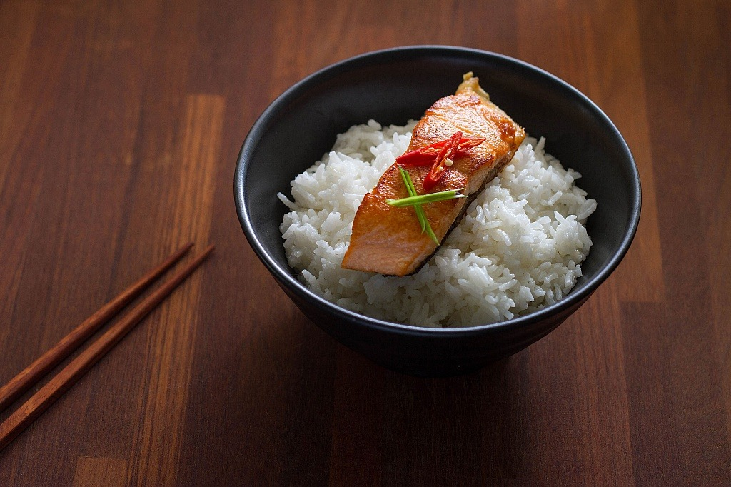 salmon over bowl of white rice