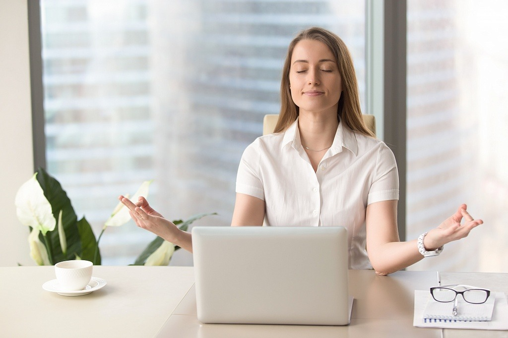 zen woman meditating in office in front of laptop
