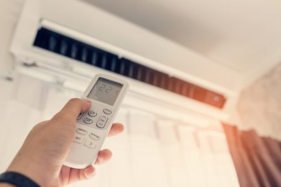man turning off air conditioning unit at home