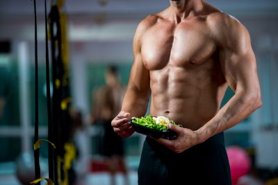 buff guy who has been using Progentra holding a plate of green salad